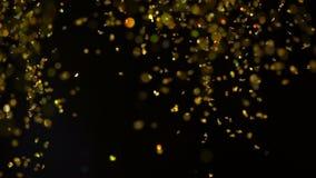 Fonkelingen in water Gouden schitter verf in water, abstracte wolkenvormingen op zwarte achtergrond Kan als glans worden gebruikt stock videobeelden