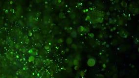 Fonkelingen in water Groen schitter verf in water, abstracte wolkenvormingen op zwarte achtergrond Kan als glans worden gebruikt stock footage