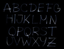 Font. Blue light alphabet on black background Stock Photography