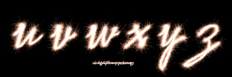 Font. Handwriting character Alphabet u,v,w,x,y,z made of sparklers font isolated on black background stock photo