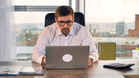 A font view on a businessman staring at a laptop screen. stock video footage