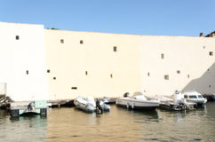 Fontage of a beige building with blue sky and boats Royalty Free Stock Photo
