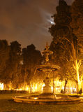 Fontain at romantic night. Romantic night near by fountain lighten by yellow light and moonlight Stock Photography