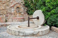 Fontaine antique et la presse d'huile en pierre images libres de droits