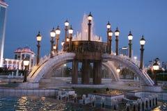 Fontaine avec des lampadaires pendant la nuit Photo stock