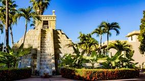 Fontaine avec la forme d'une pyramide maya entourée par les arbres et la végétation verte images libres de droits