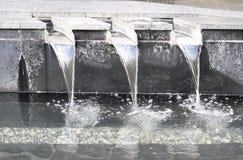 Fontaine d'eau avec les machines à paver concrètes et les canaux d'acier inoxydable images libres de droits