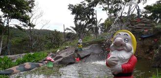 Fontaine d'eau et un Gnome de jardin avec la boîte d'arrosage devant arbres photographie stock