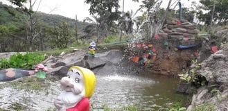 Fontaine d'eau et un Gnome de jardin avec la boîte d'arrosage devant arbres photos libres de droits