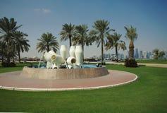 Fontaine de pot de l'eau et horizon de Doha photos stock