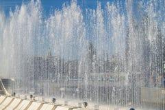 Fontaine de ville avec des jets d'eau et personnes aléatoires, la vue par le jet Photographie stock libre de droits