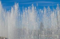 Fontaine de ville avec des jets d'eau et personnes aléatoires, la vue par le jet Images stock