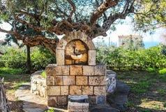 Fontaine en parc de village de petit village grec Kardamyli de Péloponnèse sous le vieil olivier avec la vue de la villa à l'arri photographie stock libre de droits