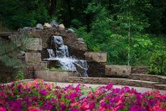 Fontaine et fleurs de cascade en parc de ville photographie stock libre de droits