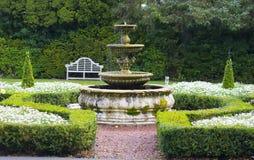 Fontaine fleurie dans de beaux jardins de pays Photographie stock