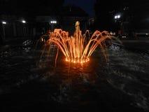 Fontaine orange dans la ville sur la rue le soir images stock