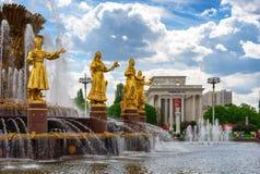Fontaine publique de l'amitié de la vue de personnes à l'exposition de parc de ville de VDNH, au ciel bleu et aux nuages à Moscou Photographie stock libre de droits