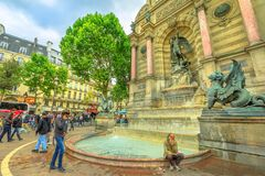 Fontaine Saint-Michel Paris. Paris, France - July 1, 2017: clochard and tourists in Place Saint-Michel and monumental Fontaine Saint-Michel with two water royalty free stock images