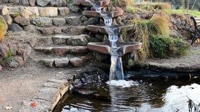 Fontana che scorre giù nel piccolo stagno nelle fasi archivi video