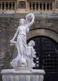 Fontana con le statue di marmo vicino ad un castello Immagine Stock