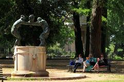 Fontana-della famiglia dei Satiri in Landhaus Borghese-Garten mit drei Frauen, die in der Nähe auf der Bank lesen lizenzfreie stockfotos