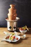 Fontana della fonduta di cioccolato con frutta fresca Immagini Stock Libere da Diritti