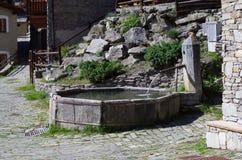 Fontana di pietra in paesino di montagna Immagine Stock