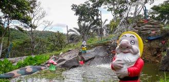 Fontana e uno Gnome del giardino con l'annaffiatoio davanti all'alberi fotografia stock libera da diritti