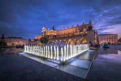 Fontana illuminata di notte, quadrato Cracovia del mercato in Polonia Fotografia Stock