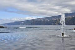 Fontana nella priorità alta e nel mare e costa di Tenerife dentro Fotografie Stock