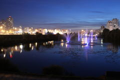 Fontana sul lago della città di sera Fotografie Stock Libere da Diritti