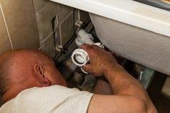 Fontanería del hombre debajo de la tina de baño imágenes de archivo libres de regalías