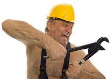 Fontanero con la llave de tubo y el casco de seguridad Imagen de archivo libre de regalías