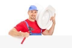 Fontanero de sexo masculino que sostiene una taza del inodoro detrás de un panel Imagen de archivo