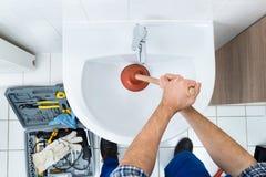 Fontanero de sexo masculino que usa el émbolo en fregadero del cuarto de baño fotografía de archivo libre de regalías