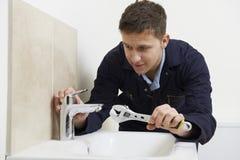 Fontanero de sexo masculino Working On Sink que usa la llave foto de archivo