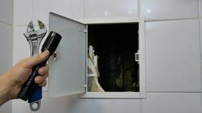 Fontanero del inspector que comprueba la tubería en la habitación almacen de metraje de vídeo