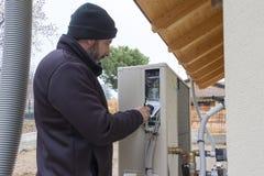 Fontanero en el trabajo que instala una pompa de calor Foto de archivo