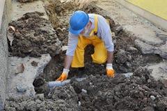 Fontanero en el tubo del alcantarillado de la reparación del emplazamiento de la obra Imagen de archivo libre de regalías