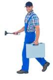 Fontanero feliz con el émbolo y la caja de herramientas que camina en el fondo blanco Foto de archivo libre de regalías
