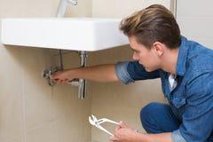 Fontanero hermoso con la llave por el fregadero en cuarto de baño Fotografía de archivo libre de regalías