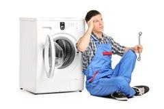 Fontanero pensativo que fija una lavadora Foto de archivo