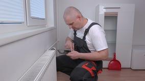 Fontanero que ajusta el radiador y que usa la tableta metrajes