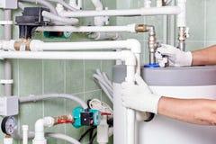Fontanero que hace los trabajos del mantenimiento para los sistemas del agua y de calefacción imagen de archivo libre de regalías