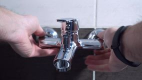 Fontanero que instala un golpecito de mezclador en un cuarto de baño, él se está sentando en el primer de la bañera almacen de video