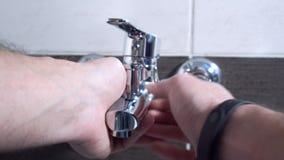 Fontanero que instala un golpecito de mezclador en un cuarto de baño, él se está sentando en la bañera, primer almacen de metraje de vídeo