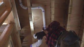 Fontanero que pega el tubo blanco del retrete plástico en cierre encima del tiro almacen de metraje de vídeo
