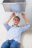 Fontanero que repara el dren del lavabo en cuarto de baño Imagen de archivo libre de regalías