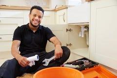 Fontanero que se sienta en una cocina, retrato de la raza mixta foto de archivo