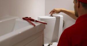 Fontanero que trabaja en el cuarto de baño que instala el tanque de agua del wc almacen de metraje de vídeo